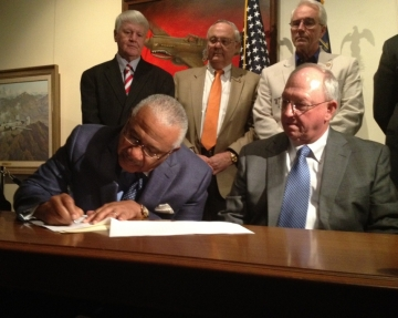Bibb County Commission Chair Sam Hart signs Encroachment agreement while Houston County Commission Chair Tommy Stalnaker and other elected officials look on (photo Josephine Bennett)