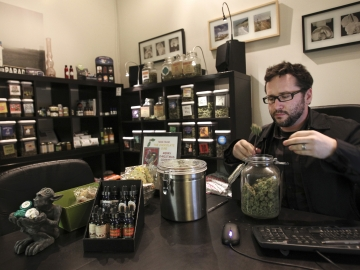 Chris Guthrie, vice president for operations at Canna Pi medical dispensary, inspects a medical marijuana product at his clinic in Seattle on Monday. Marijuana will be legal in Washington state from 12:01 a.m., Thursday.