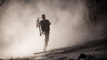 A Free Syrian Army fighter runs after attacking a tank with a rocket-propelled grenade in Aleppo, Syria on Friday. The situation in Syria is just one of several tense situations in the Middle East whoever wins the U.S. presidential election in November will be faced with.