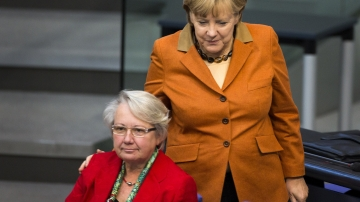German Chancellor Angela Merkel puts her hands on the shoulder of Education Minister Annette Schavan during a session of the Bundestag, the German lower house of parliament, in Berlin, on Oct. 18, 2012. Merkel gave guarded support to Schavan, who is facing calls to resign over allegations of plagiarism.