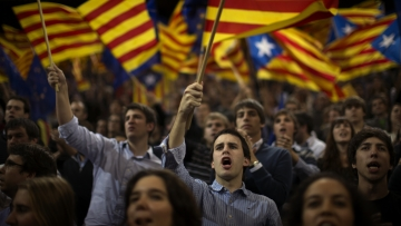 Supporters of center-right Catalan Nationalist Coalition leader, Artur Mas, wave pro-independence flags during the last day of campaigning in Barcelona, Spain, on Friday.
