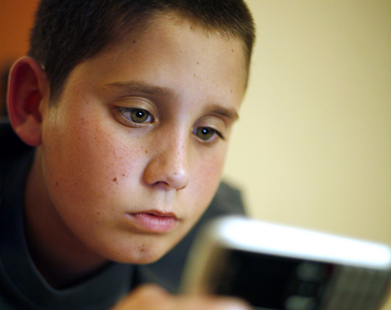 An image of a child absorbed in using a consumer electronic.