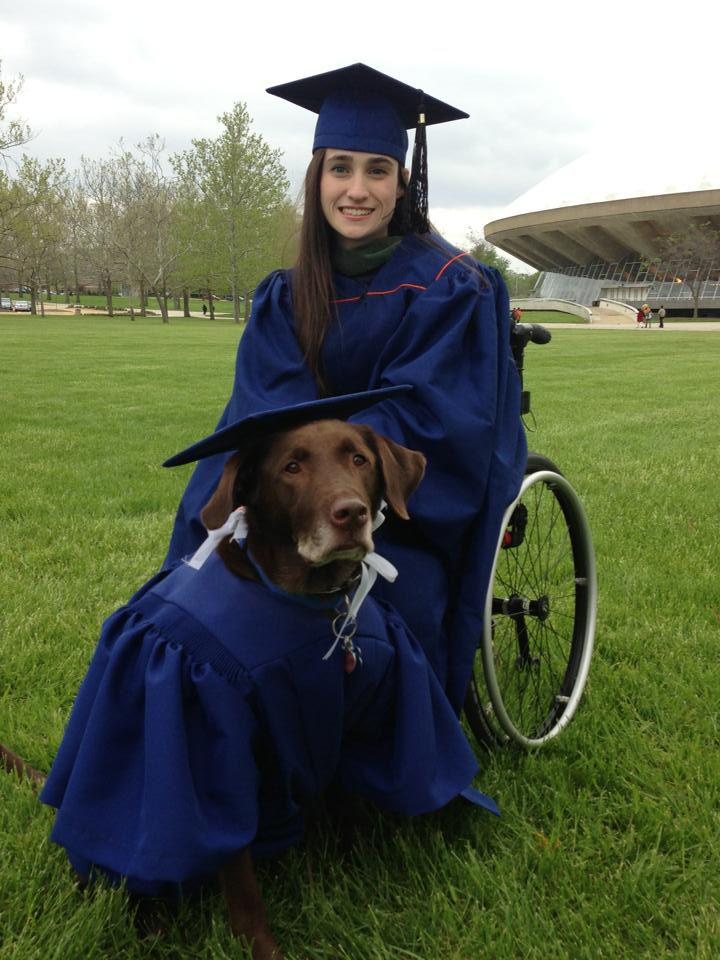 graduate and dog hero pose together