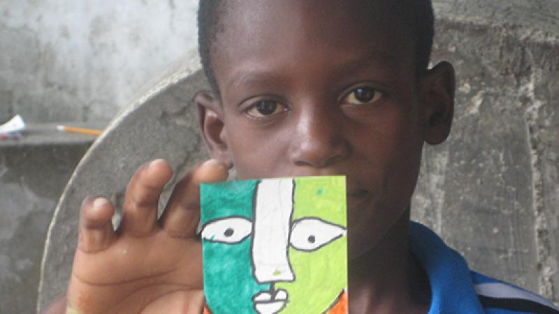 A Haitian student from Project Hope ART holds up his artwork. (Photo courtesy Karen Packer.)