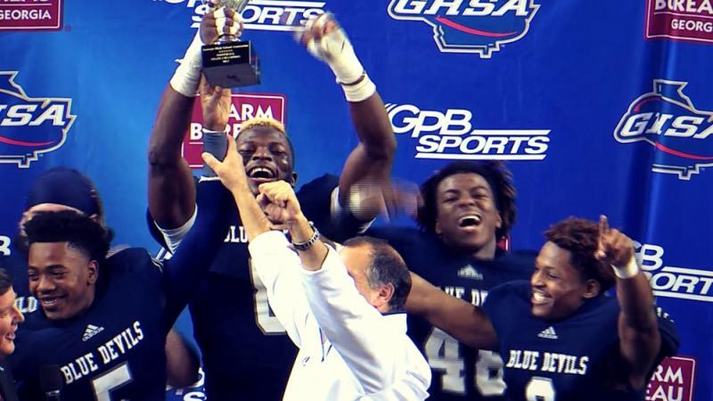 The Norcross Blue Devils hoist the 2013 Class AAAAAA state title trophy.