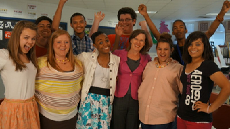 Anne Ostholthoff smiles alongside students from Columbus High School in the premiere episode of The Ignite Show.
